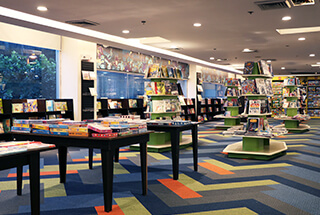 Fully Booked's store filled with books and tables and a colorful carpet